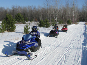 3 snowmobiles move quickly down a snowy trail