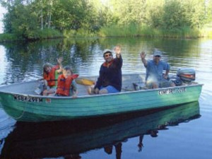A family waves to the camera from a motorized boat on the water
